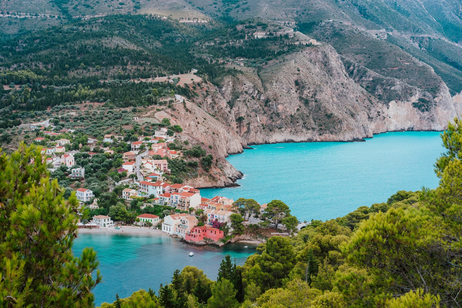Assos village at Kefalonia island, Greece. Beautiful colorful town at shore with bay lagoon, pine and cypress trees, rocky coastline